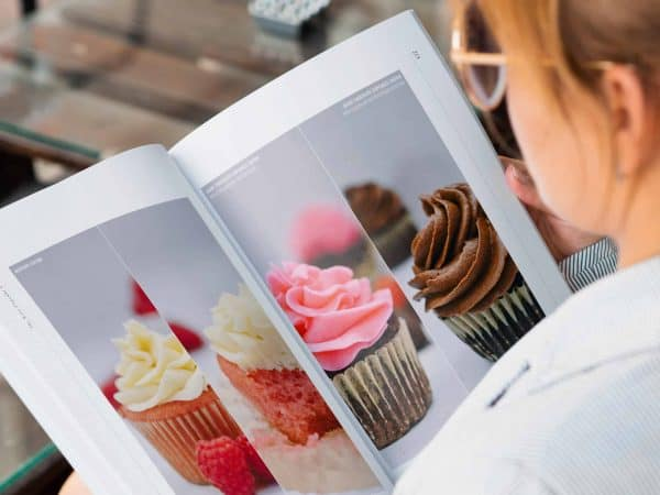 woman flipping through image gallery in keto cupcake cookbook